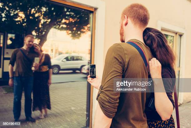Caucasian couple taking self portrait in mirror