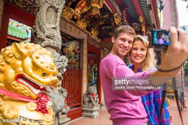 Caucasian couple taking selfies at Tan Si Chong Su temple, Singapore