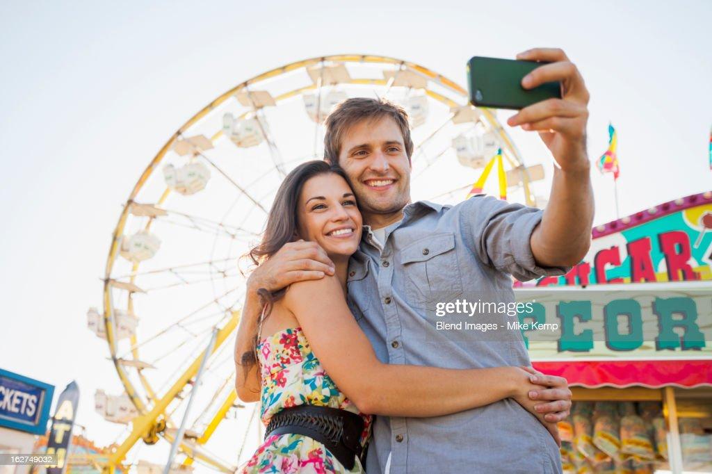 Caucasian couple taking self-portrait at carnival : Stock Photo