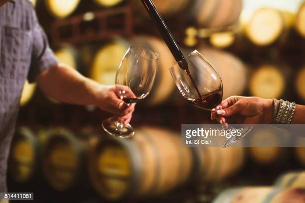 Caucasian couple tasting wine in cellar