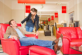 Caucasian couple testing armchair in furniture store