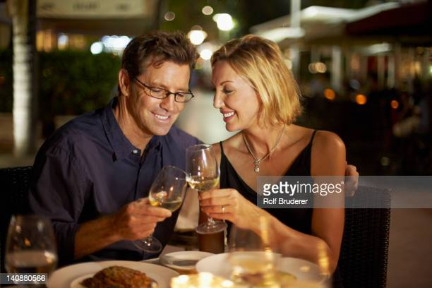 Caucasian couple toasting with wine in restaurant