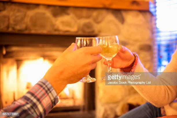 Caucasian couple toasting with wine near fireplace