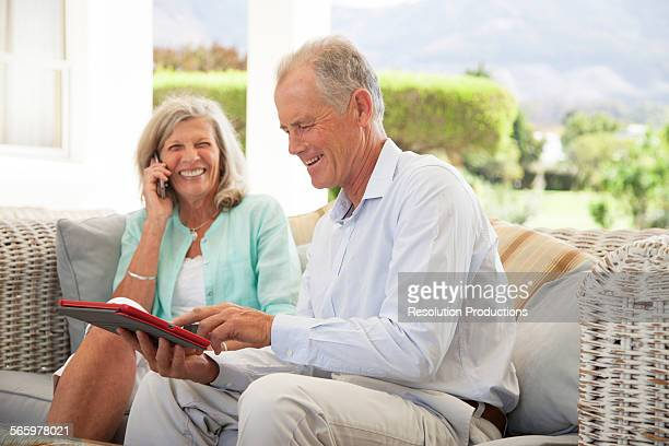 Caucasian couple using cell phone and digital tablet on sofa