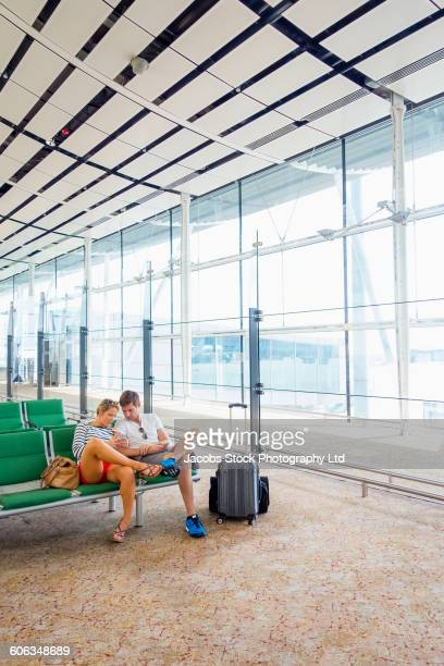 Caucasian couple using cell phone in airport