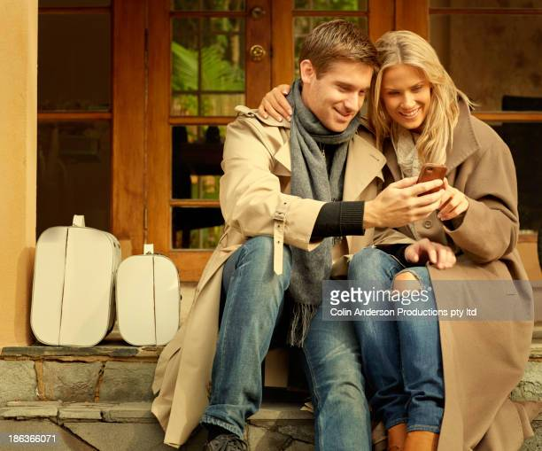 Caucasian couple using cell phone together on porch