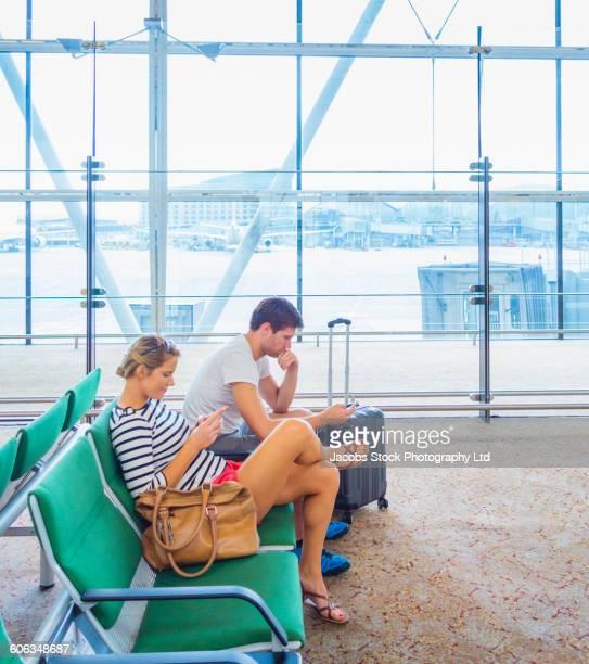 Caucasian couple using cell phones in airport