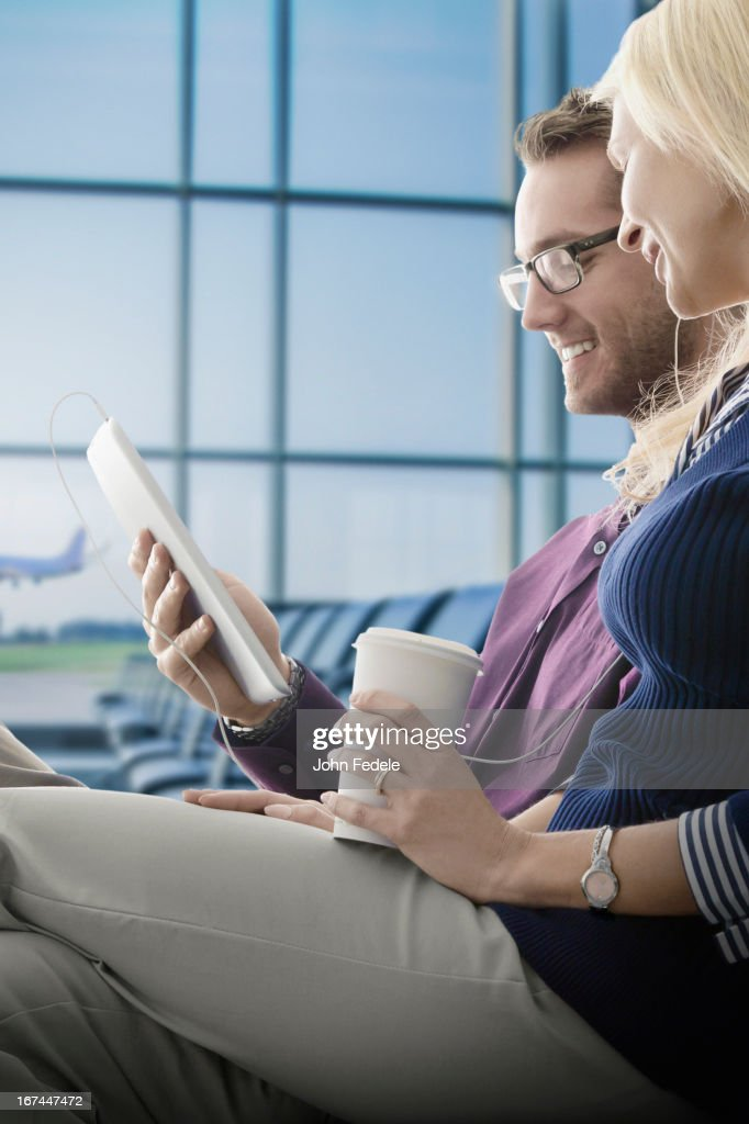 Caucasian couple using digital tablet in airport : Stock Photo