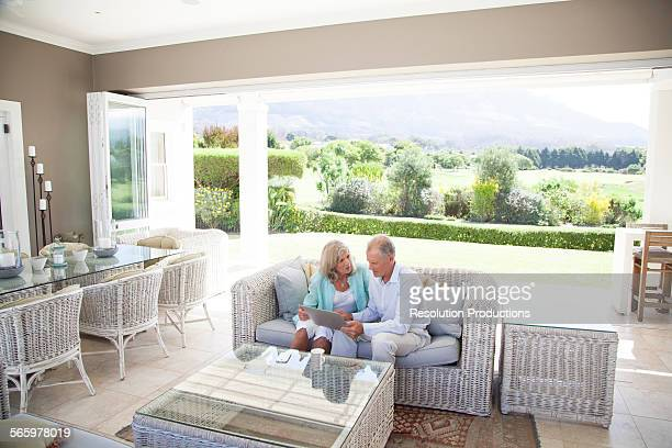 Caucasian couple using digital tablet on sofa