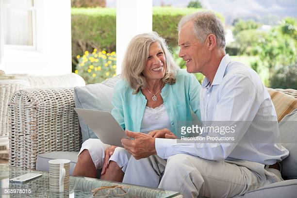 Caucasian couple using laptop on sofa outdoors