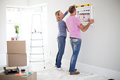Caucasian couple using level in new home