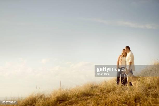 Caucasian couple walking dog on grassy dunes