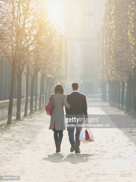 Caucasian couple walking in urban park