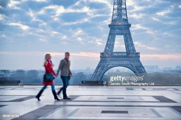 Caucasian couple walking near Eiffel Tower, Paris, Ile-de-France, France