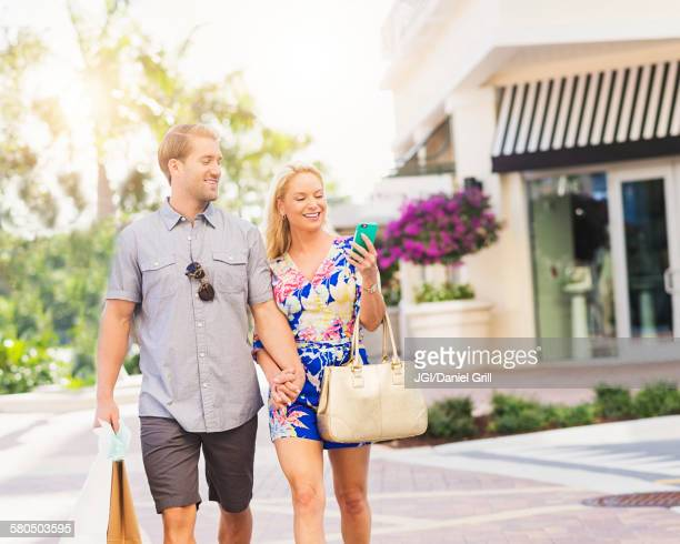 Caucasian couple walking on city sidewalk