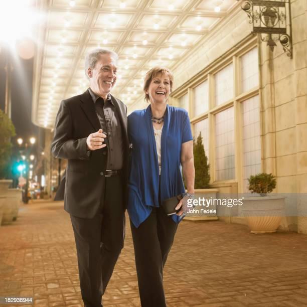 Caucasian couple walking on city street