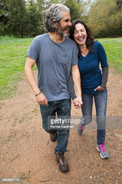 Caucasian couple walking on dirt path in park