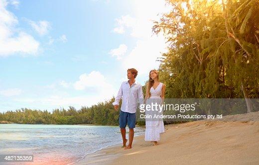 Caucasian couple walking on tropical beach