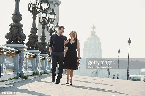 Caucasian couple walking on urban bridge