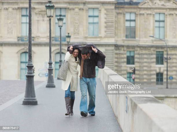 Caucasian couple walking under jacket in rain on urban bridge