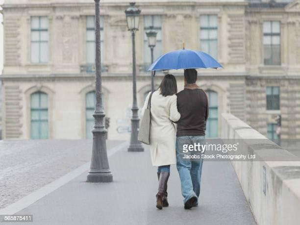 Caucasian couple walking under umbrella in rain on urban bridge