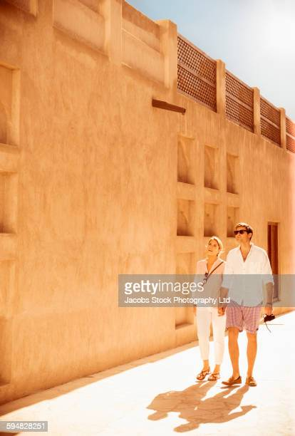 Caucasian couple walking under wall