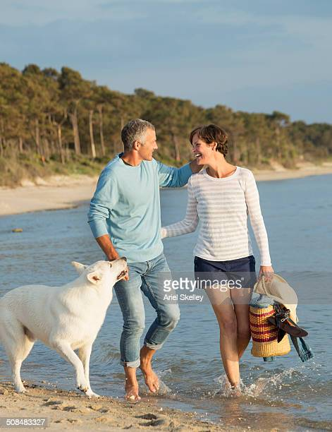 Caucasian couple walking with dog on beach