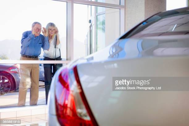 Caucasian couple window shopping for cars outside dealership