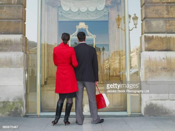 Caucasian couple window shopping on city sidewalk