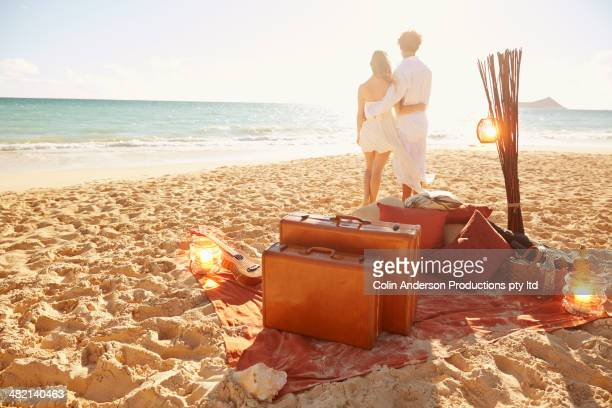 Caucasian couple with suitcases on tropical beach