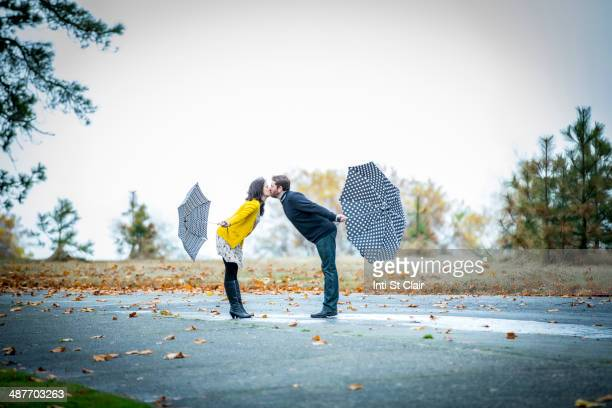 Caucasian couple with umbrellas kissing outdoors