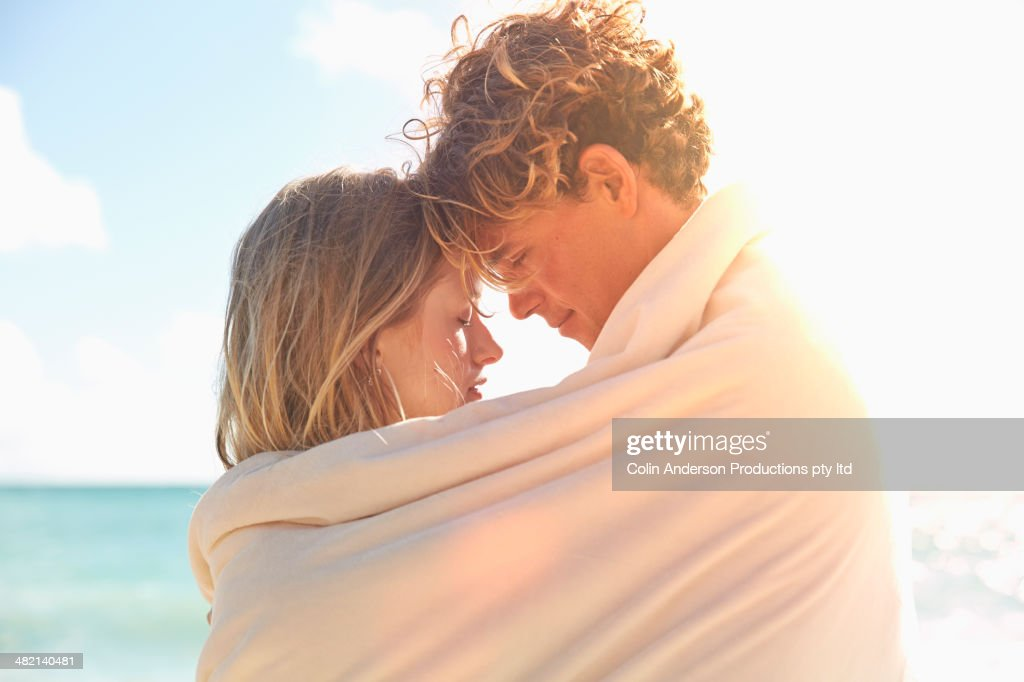 Caucasian couple wrapped in blanket on beach