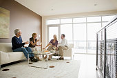 Caucasian couples drinking wine in modern living room