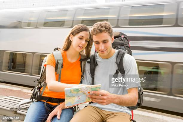Caucasian couples sitting on bench near train reading map