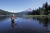 Caucasian Cowboy Fly Fishing In A Mountain Lake