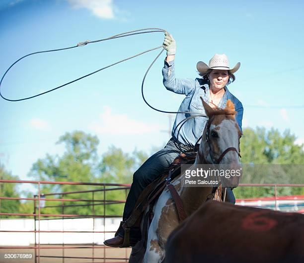 Caucasian cowgirl on horse throwing lasso on ranch