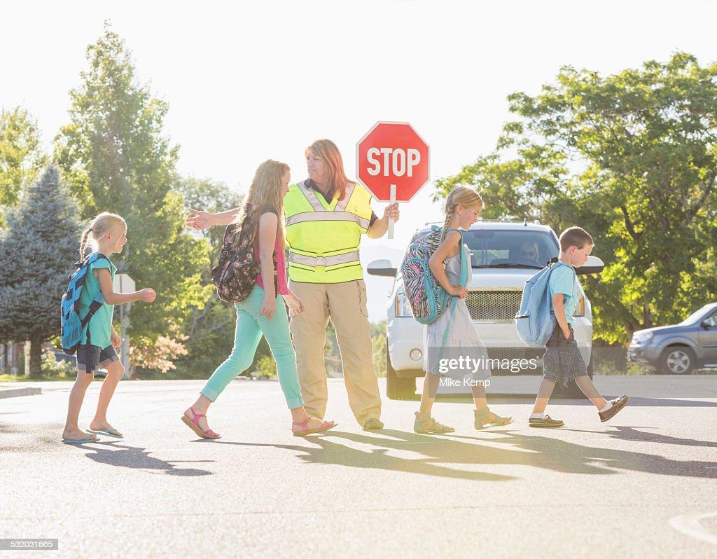 Caucasian crossing guard helping children in crosswalk