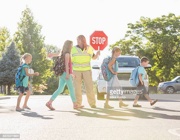 Caucasian crossing guard helping children in crosswalk