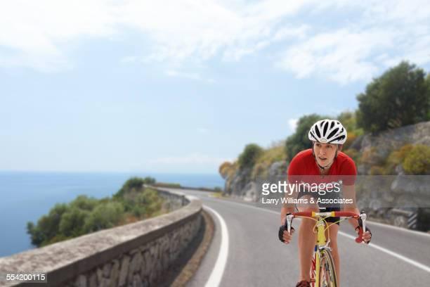 Caucasian cyclist biking on remote coastal road