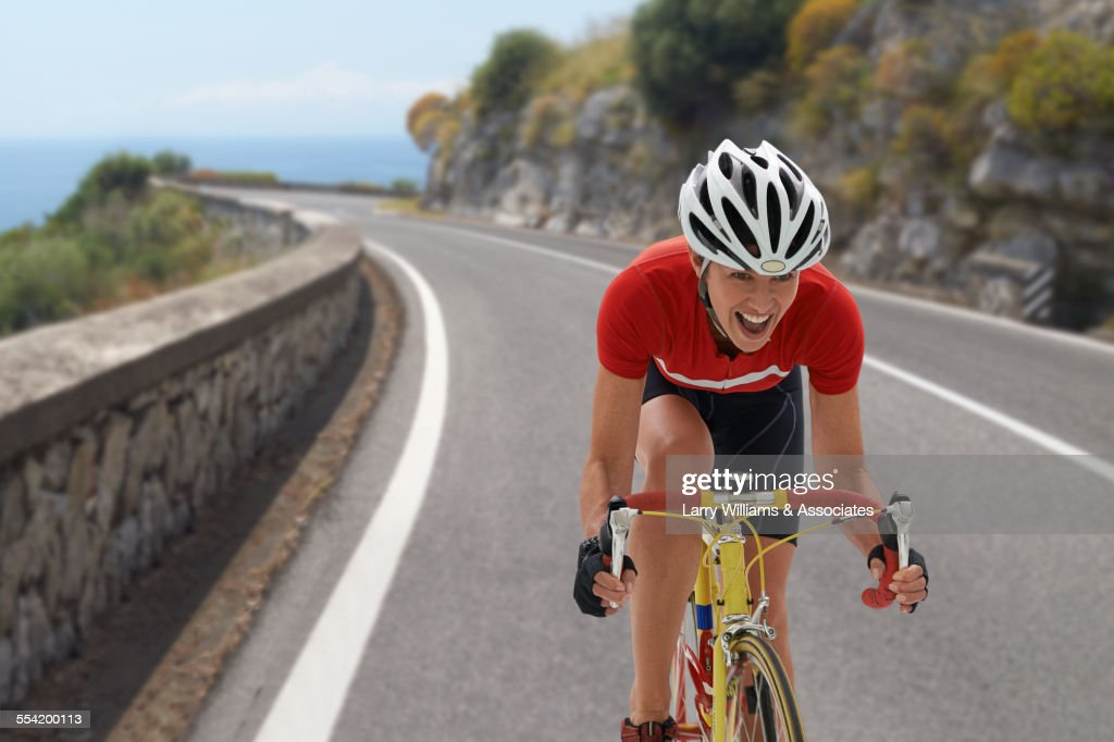Caucasian cyclist cheering on remote coastal road : Stock Photo