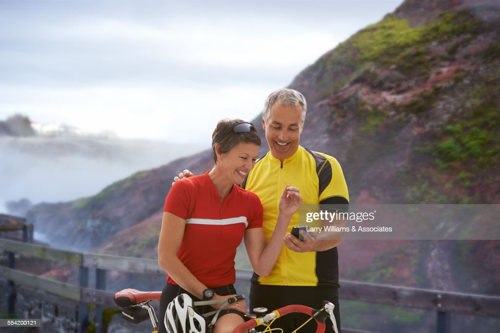 Caucasian cyclists using cell phone on remote coastal road