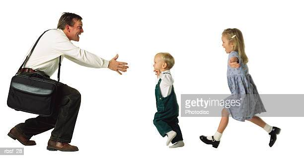 caucasian dad just got home from work and has his arms outstretched with a briefcase on shoulder while his two blonde kids run to greet him