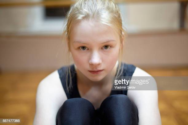 Caucasian dancer sitting on studio floor