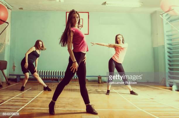 Caucasian dancers rehearsing in gym