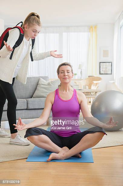 Caucasian daughter annoying meditating mother in living room