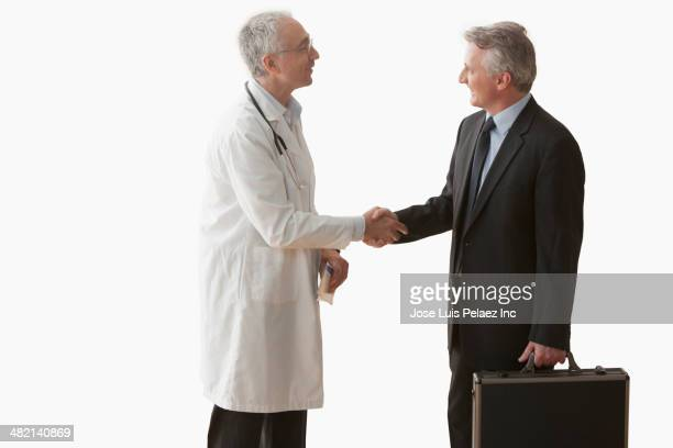 Caucasian doctor and businessman shaking hands
