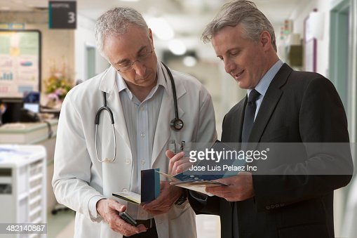 Caucasian doctor and businessman talking in hospital