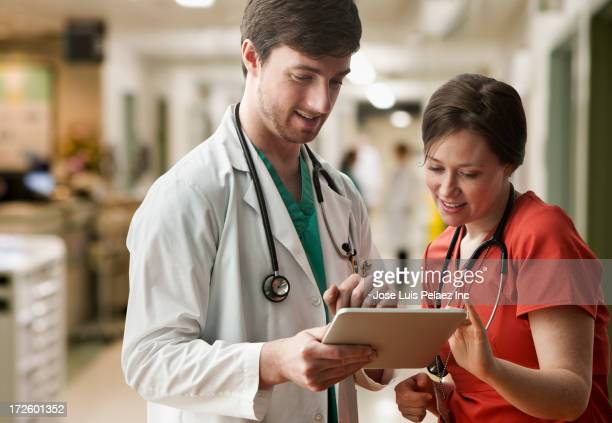 Caucasian doctor and nurse using tablet computer