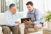 Caucasian doctor and patient using digital tablet at home