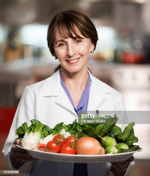 Caucasian doctor holding platter of vegetables